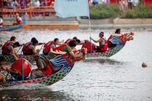 Two dragon boats racing, neck and neck with each other