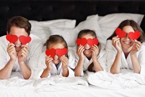 Family at hotel holding red valentine hearts over their eyes